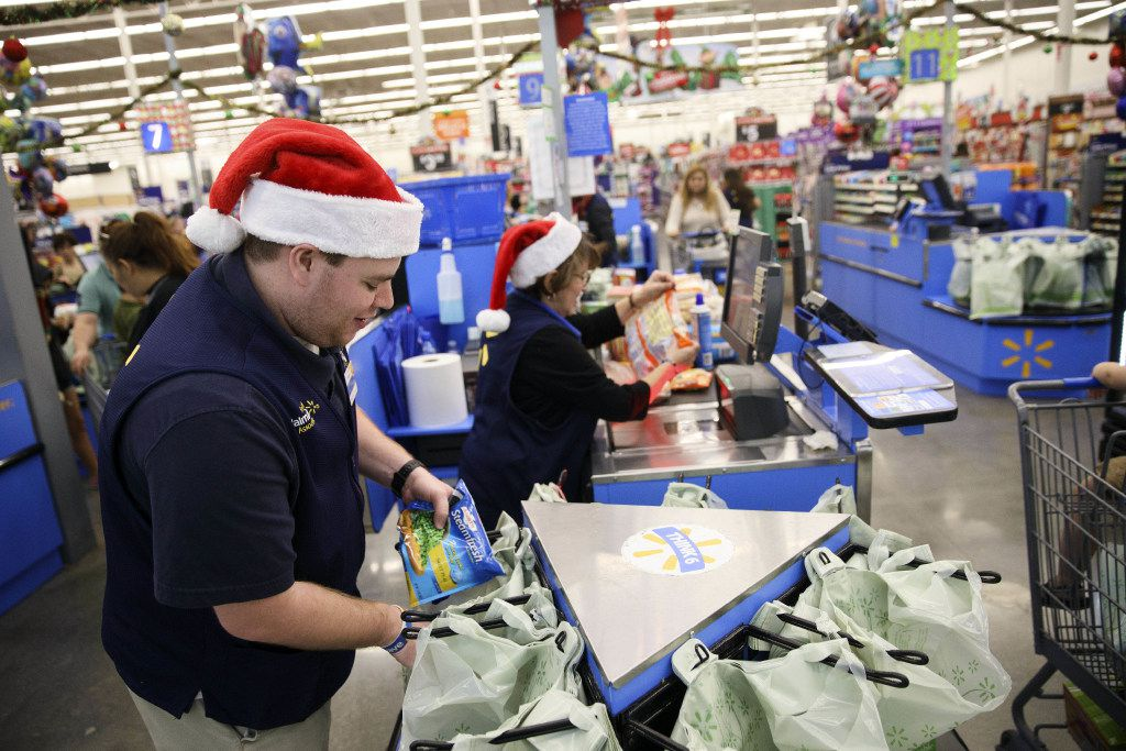 An employee places an item into a shopping bag at a Wal-Mart in Burbank, California, on Nov. 22, 2016. MUST CREDIT: Bloomberg photo by Patrick T. Fallon.