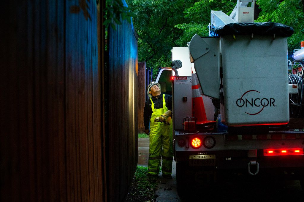 Freddy Diaz, a troubleshooter with Oncor Electric Delivery, examines a fallen tree branch that caused a blown fuse in the Junius Heights neighborhood in Dallas after a severe thunderstorm caused power outages throughout the city on Sunday, June 16, 2016.