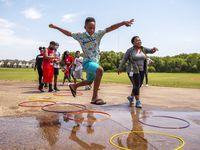 Samuel Ramsey, 12, leaps over a puddle of water to a hula-hoop during a game that included hopscotch and paper-rock-scissors, at the Frazier Revitalization pop-up summer camp at the Frazier Townhomes Community in Dallas, July 15, 2020.