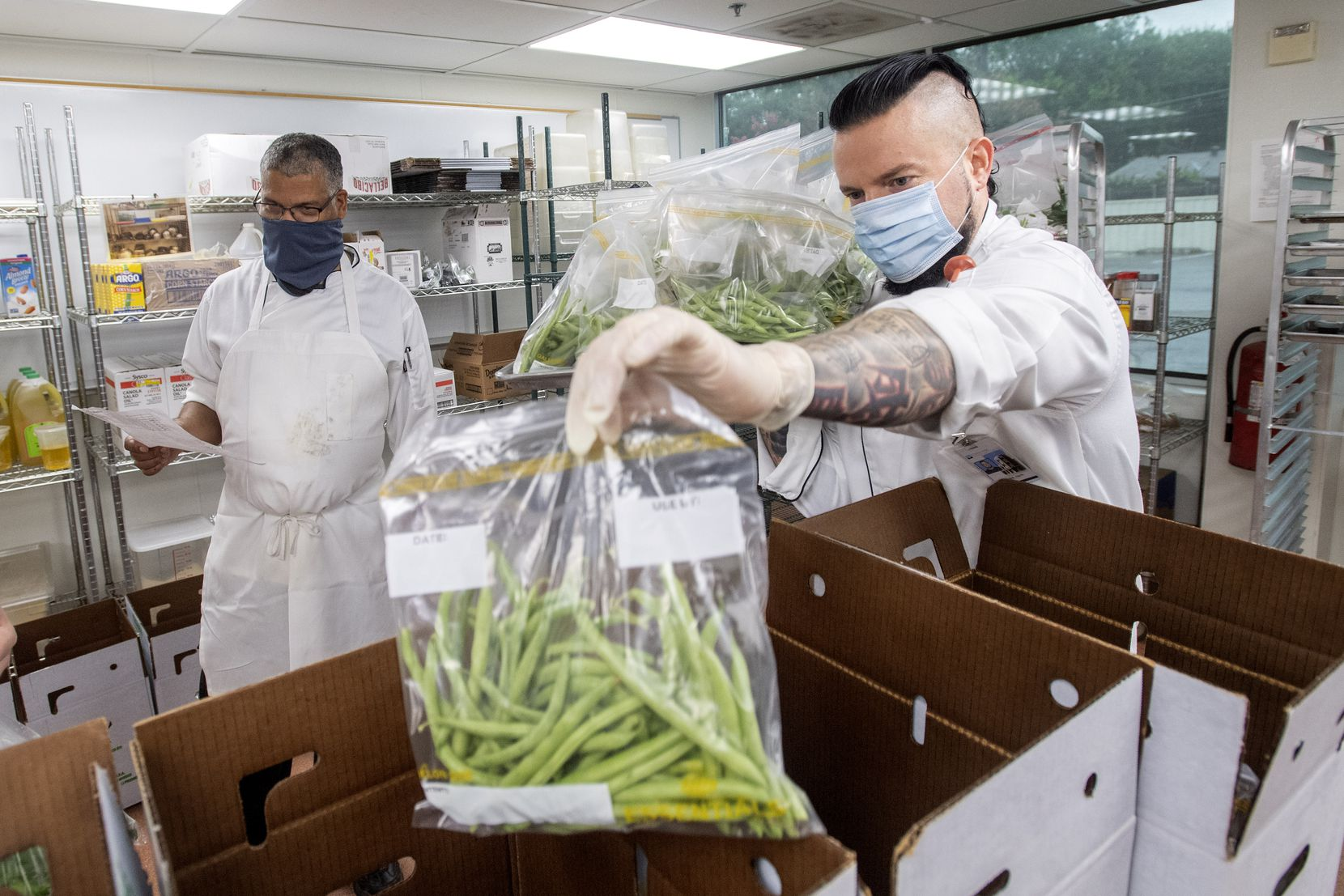 Patrick Stark (right), an instructional specialist at the Dallas College Culinary, Pastry and Hospitality Center, loads green beans into boxes of ingredients as instructional dean Brian Hay looks on.