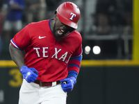 Texas Rangers center fielder Adolis Garcia celebrates as he rounds the bases after hitting a solo home run to tie the game during the seventh inning against the Minnesota Twins at Globe Life Field on Friday, June 18, 2021.