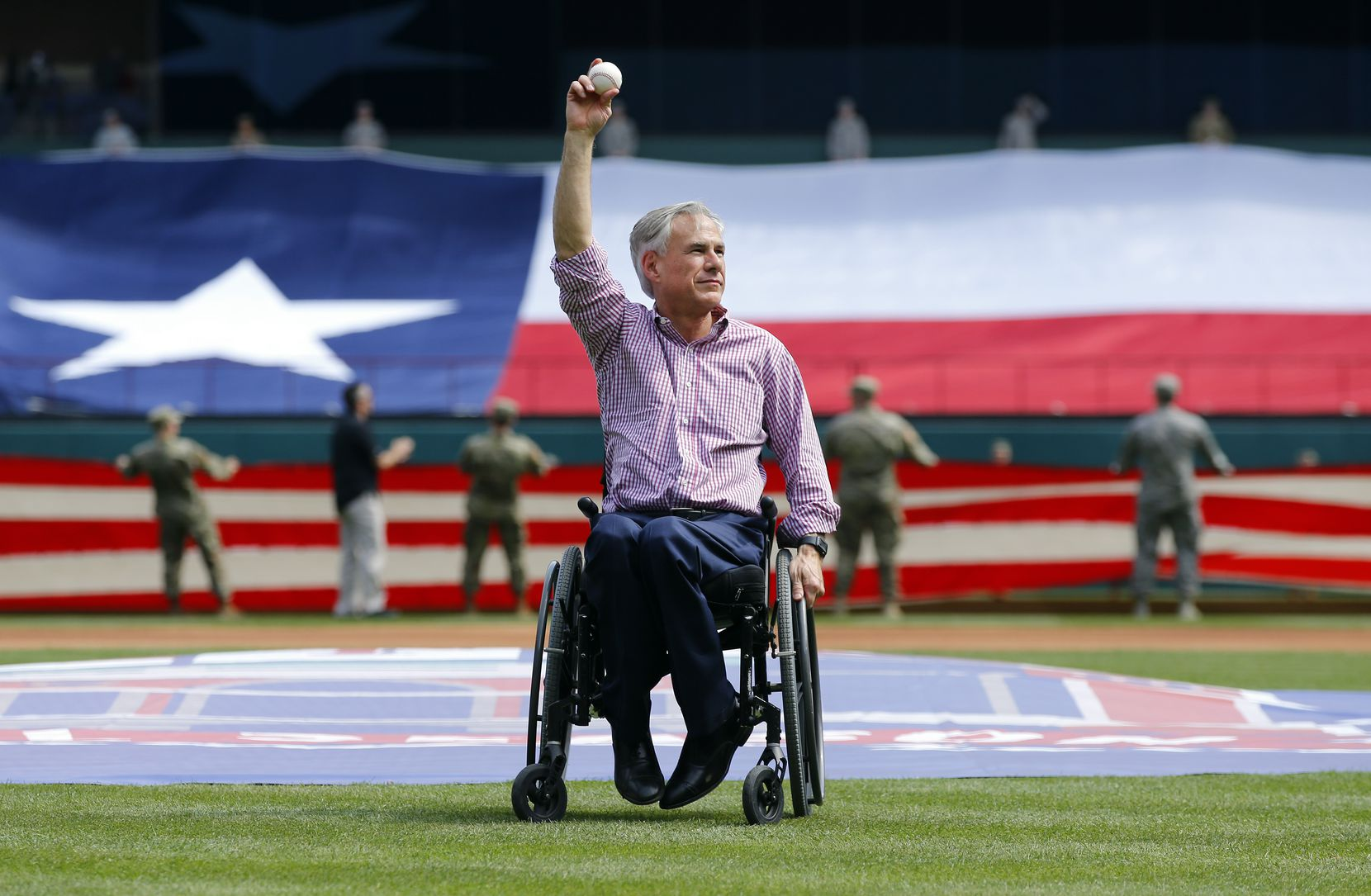 Gov. Greg Abbott, shown waving to the crowd before he threw out the ceremonial first pitch during the Texas Rangers' March 2019 season opener, will videotape a first pitch. The video will be shown at Friday evening's Rangers opener at the club's new Globe Life Park in Arlington.