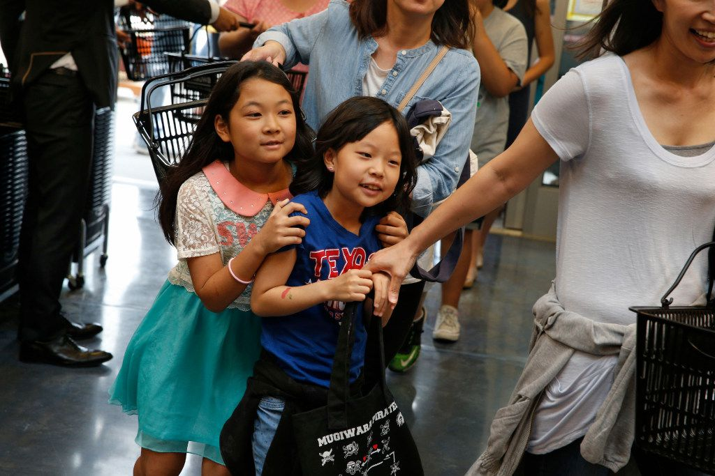 Lenna Kikuma, 10, (left) and Hana Kim, 8 are some of the first customers enter during the grand opening of the Mitsuwa Market place in Plano, Texas on April 14, 2017. (Nathan Hunsinger/The Dallas Morning News)