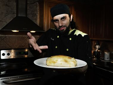 Local chef and hip-hop DJ Julio Cordonnier poses with an empanada at his home in Euless.