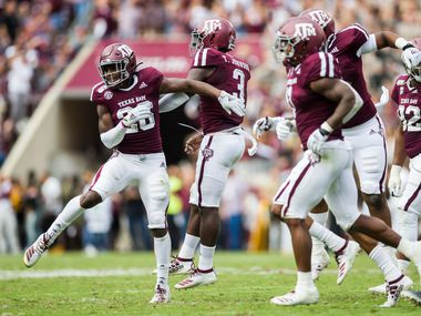 Texas A&M Aggies defensive back Demani Richardson (26) celebrates an interception with Texas A&M Aggies defensive lineman Tyree Johnson (3) during the second quarter of a college football game between Texas A&M and Alabama on Saturday, October 12, 2019 at Kyle Field in College Station, Texas. (Ashley Landis/The Dallas Morning News)