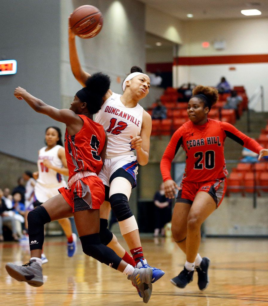 Duncanville's Zaria Rufus (12) passes the ball off to a teammate as she's cutoff by Cedar Hills' Carolynn Washington (5) during the first half of the Class 6A Region I championship game at Wilkerson-Greines Activity Center in Fort Worth, Saturday, February 29, 2020. (Tom Fox/The Dallas Morning News)