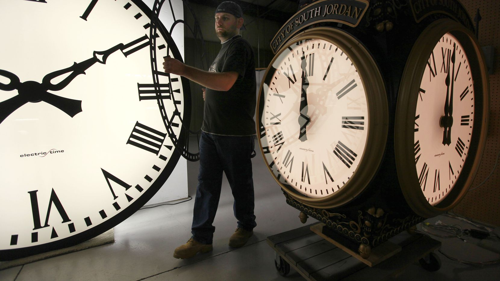 Dan LaMoore of Electric Time Co. moves a clock face at his plant in Medfield, Mass., between a large tower clock (left) bound for King of Prussia, Pa., and a post clock headed to South Jordan, Utah. Daylight Savings Time ends on at 2 a.m. Sunday, when clocks will be set back one hour.  (2011 File Photo)