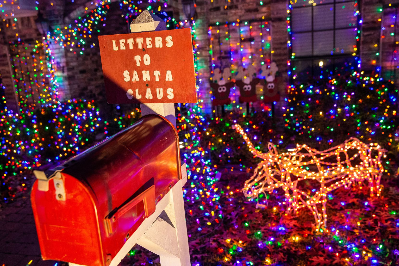 """Jim and Linda Shultz's """"Letters to Santa"""" mailbox sits near their University of Texas Longhorn, just one of many characters in their holiday display."""