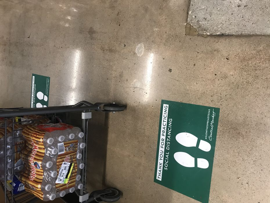 Central Market and H-E-B stores in Texas have added decals on the floor to remind shoppers to keep their distance during the coronavirus pandemic. While shopping at most other stores has stopped or is limited to curbside or abbreviated hours, grocery stores and drugstores are busier than ever.
