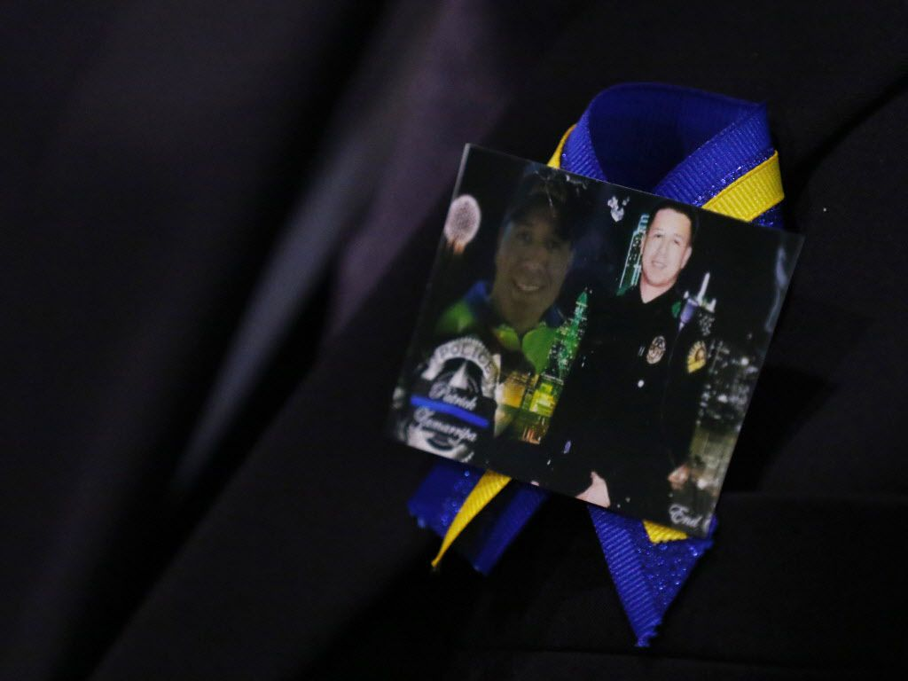 A family member wears a ribbon with photos of Patrick Zamarripa during a funeral service for the slain Dallas police officer.
