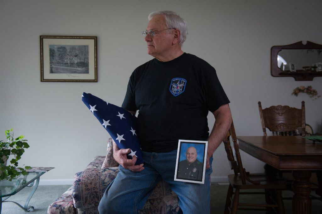 William Ahrens holds a portrait of his son Lorne Ahrens, who was killed in the line of duty as a Dallas police officer a year ago, at his home in Eagle River, Alaska.