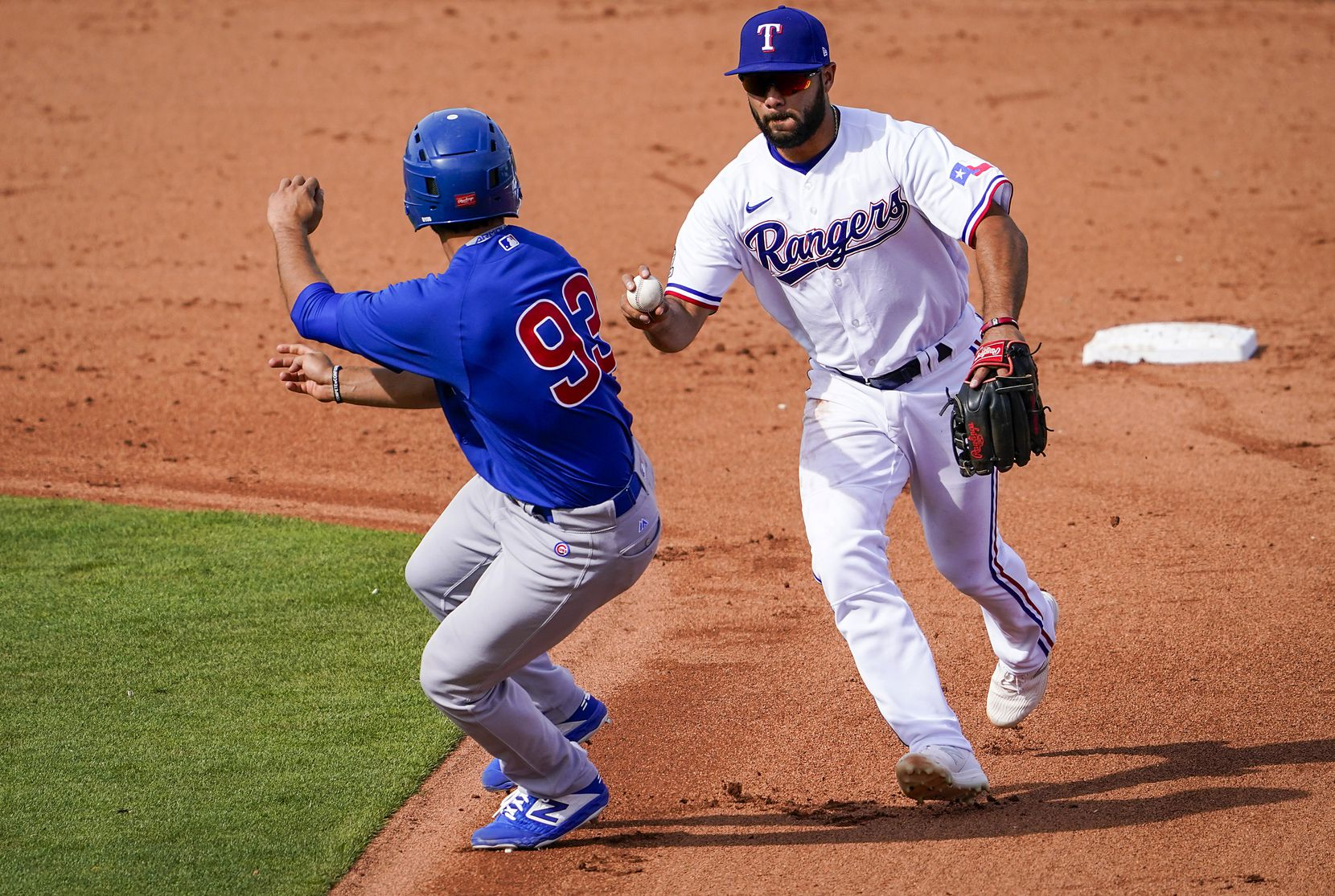 Texas Rangers shortstop Isiah Kiner-Falefa chases down the Chicago CubsÕ Alfonso Rivas to apply the tag and start a double play on a grounder by Ian Miller during the sixth inning of a spring training game at Surprise Stadium on Thursday, Feb. 27, 2020, in Surprise, Ariz.
