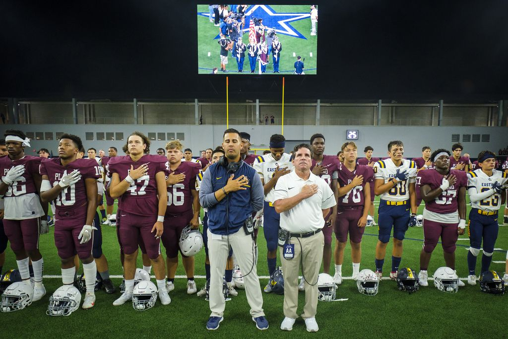 Plano head coach Jaydon Mccullough (right) and El Paso Eastwood head coach Julio Lopez join their players as they stand for the national anthem at midfield before a high school football game at The Star on Thursday, Sept. 5, 2019, in Frisco, Texas. The game was originally canceled after a former Plano student allegedly killed 22 people in a shooting at an El Paso Walmart. The game was reinstated after Plano ISD received pushback on its original decision.(Smiley N. Pool/The Dallas Morning News)