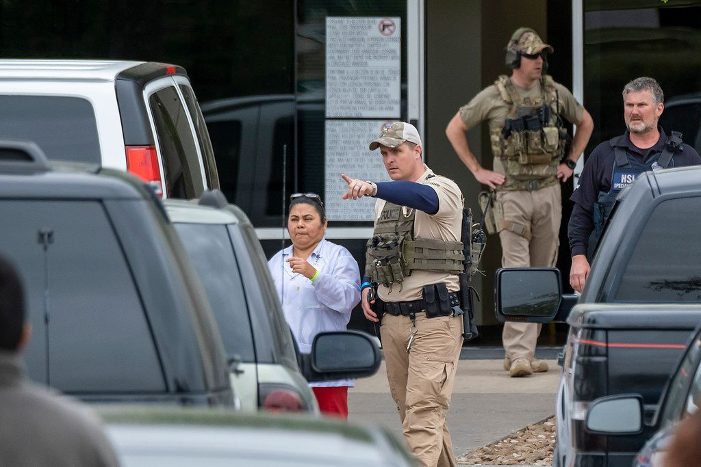 A woman wearing a green wristband was escorted by U.S. Immigration and Customs Enforcement officials away from CVE Group on Wednesday in Allen.