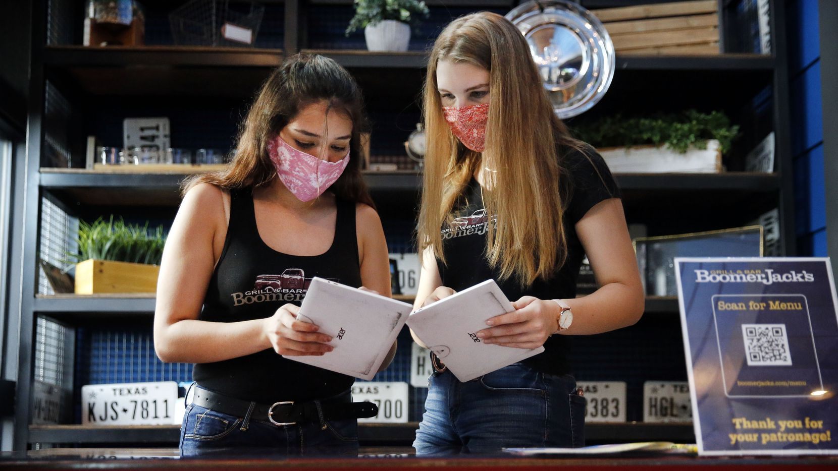 Hostesses Leslie Valdez (left) and Kylie Ellis check on tables at BoomerJack's Grill and Bar in Grapevine on Aug. 27.