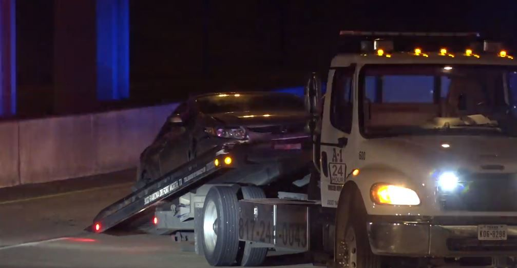 A silver Honda is loaded onto a tow truck after it crashed during a high-speed police chase Thursday morning that began in Springtown and ended in Fort Worth.