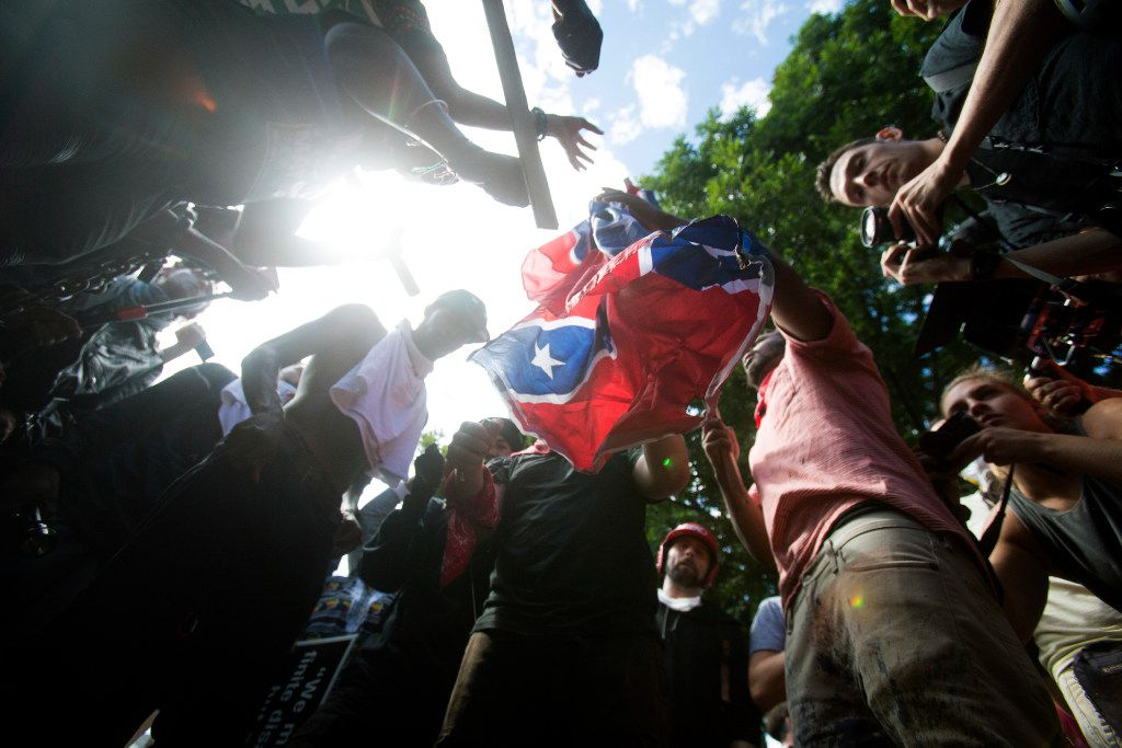 Counter-protesters tear a Confederate flag during a white nationalist rally, on Saturday Aug. 12, 2017, in Charlottesville, Va.  (Shaban Athuman /Richmond Times-Dispatch via AP)