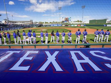 Texas Rangers players stand for the national anthem before a spring training game against the and the Kansas City Royals in their Cactus League opener at Surprise Stadium on Sunday, Feb. 28, 2021, in Surprise, Ariz.