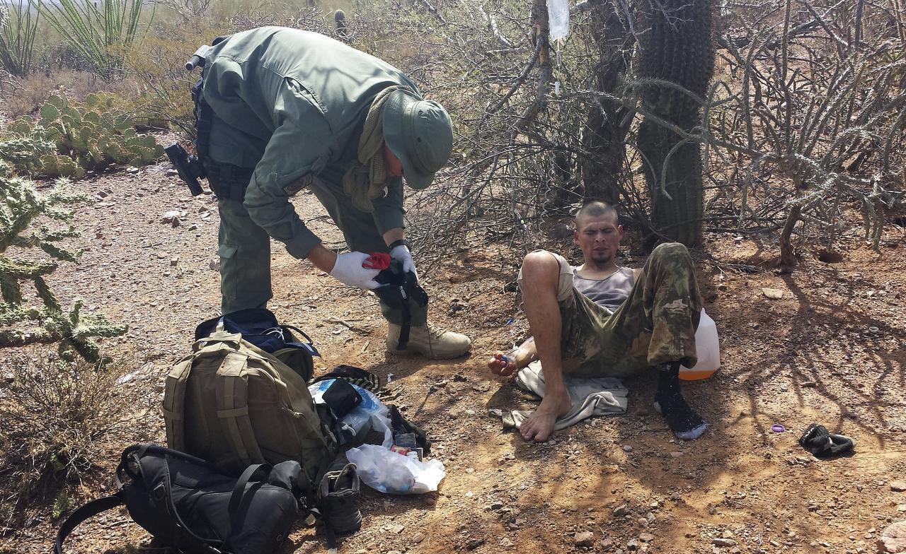 Un agente de la Patrulla de Fronteras asiste a un migrante que fue encontrado deshidratado cuando intentaba cruzar ilegalmente la frontera entre México y Estados Unidos cerca de Sells, Arizona. Foto: AP