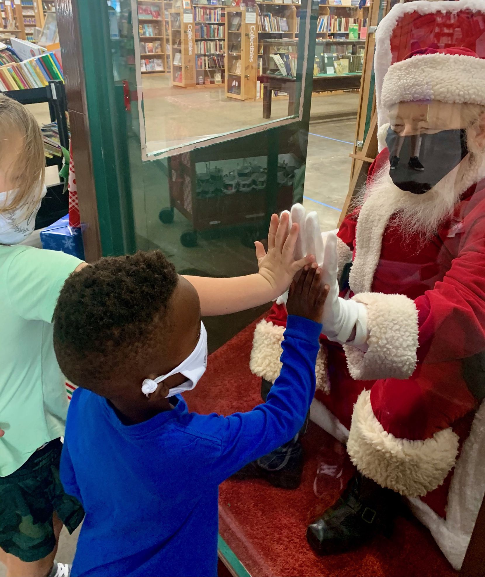 Scott Ward, the longtime Santa at Half Price Books, connects with children who came to see Santa through a protective screen at the retailer's flagship store in Dallas.
