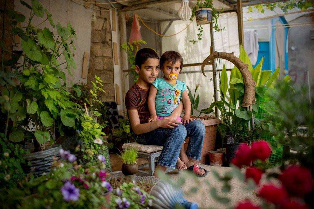 A brother and sister are surrounded by plants as they sit on a porch at the Domiz refugee camp. The camp in northern Iraq was established in 2012 and provides shelter for primarily Syrian Kurds.
