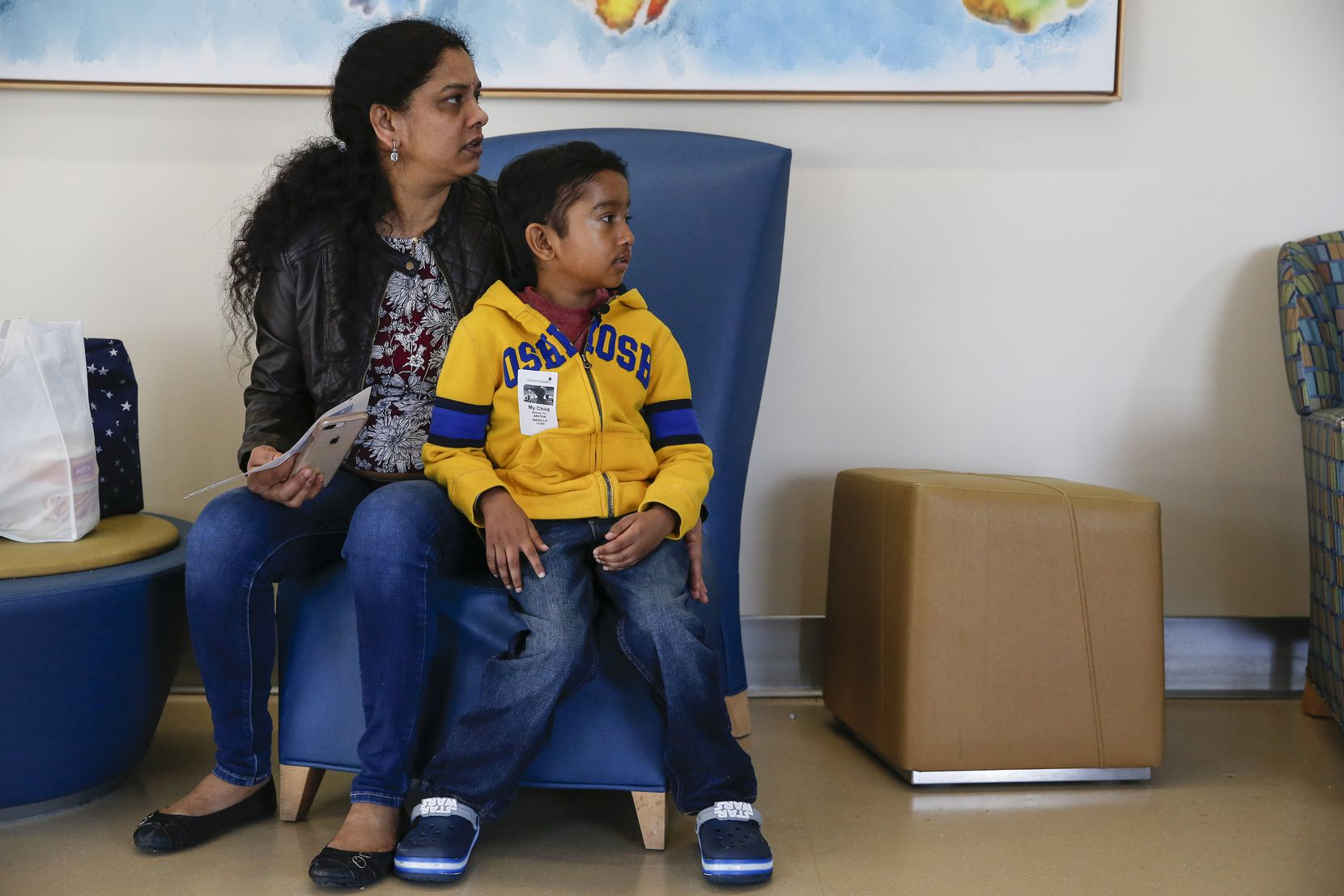 Akshaj Nagilla, 8, of Frisco, sits in a waiting room with his mother Anitha Nagilla, as they walk down the hallway to an appointment at Children's Medical Center Dallas on Friday, Feb. 7, 2020 in Dallas. In 2017, when Akshaj was six years old, he was diagnosed with leukemia and in desperate need of a bone marrow transplant. In August of 2017, he received his first transplant through the Be The Match donor program, which his family believes saved his life. After a relapse of the cancer in 2018 he needed a new transplant, which he received two days after Christmas in 2018. Today, Akshaj is now 8 years old and is still in remission, often visiting Children's Medical Center for checkups and blood work. (Ryan Michalesko/The Dallas Morning News)