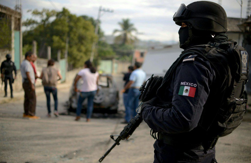 A police officer stands guard as personnel of Guerrero state attorney's office work next to a car which was found with three calcined bodies inside in the outskirts of Acapulco, Guerrero state, Mexico, on January 25, 2018.  Nearly 19,000 people have been killed due to organized crime in Mexico in 2017, the most violent year in twenty years, according to a report revealed Tuesday by the Mexican NGO Semaforo Delictivo. Guerrero is one of Mexico's poorest and most violent states, where a lucrative drug trade has flourished.