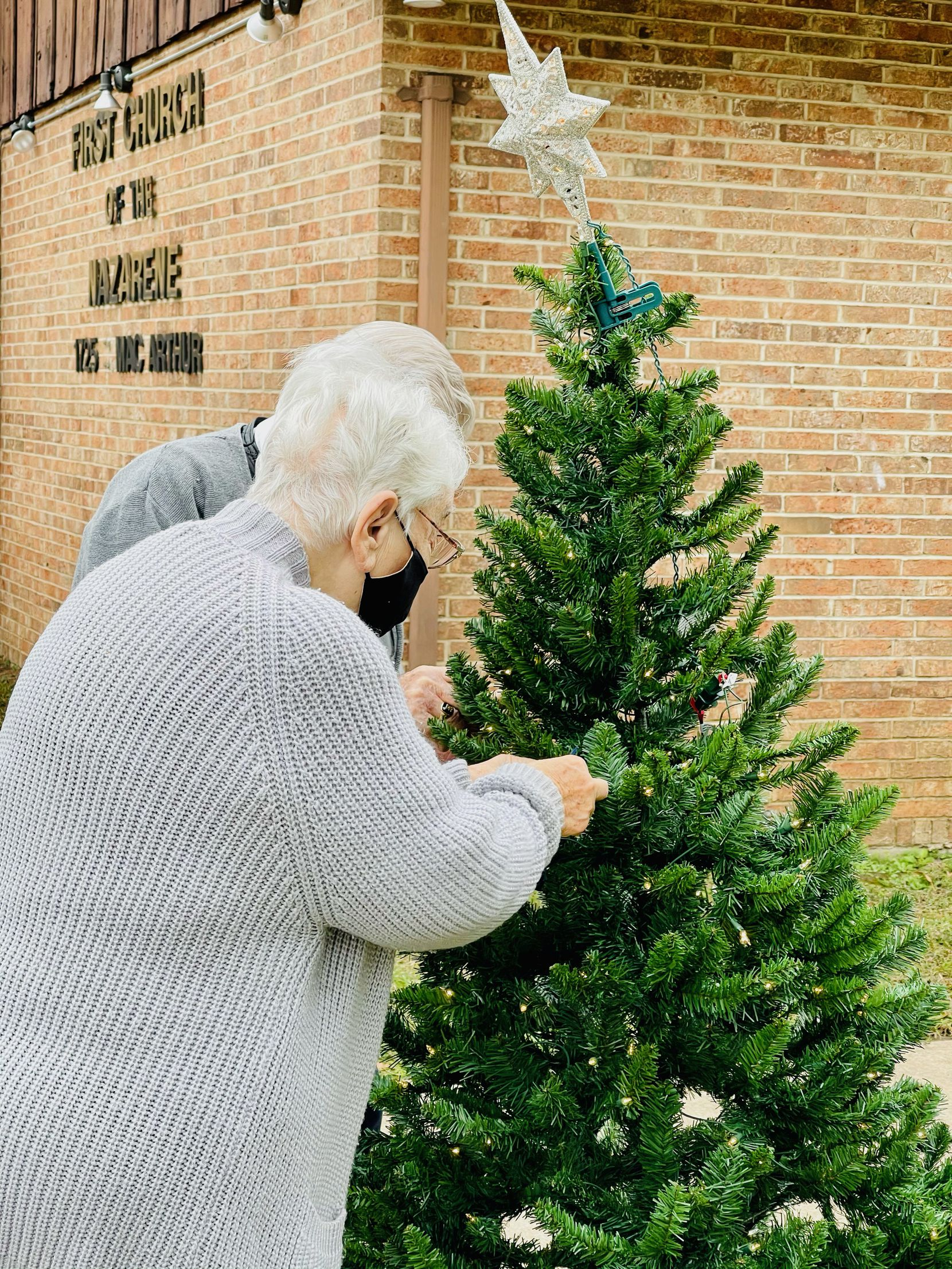 Visitors hang ornaments from trees outside Irving First Church of the Nazarene.