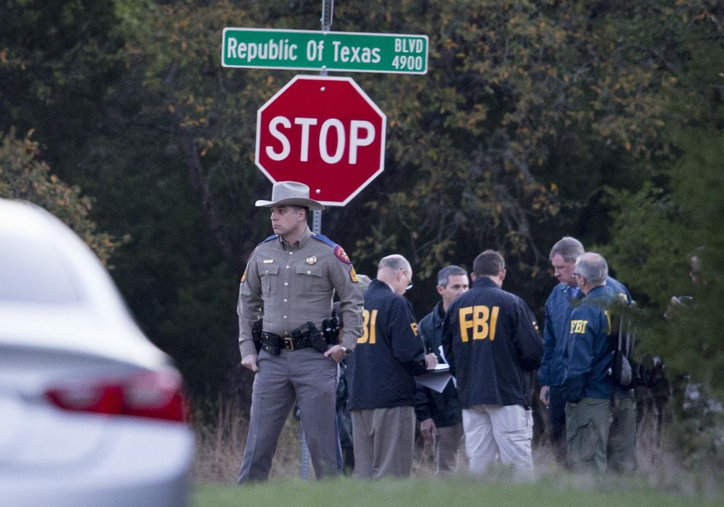 Law enforcement officers gather at the intersection of Republic of Texas and Mission Oaks boulevards in the Austin to investigate a bombing on Monday.