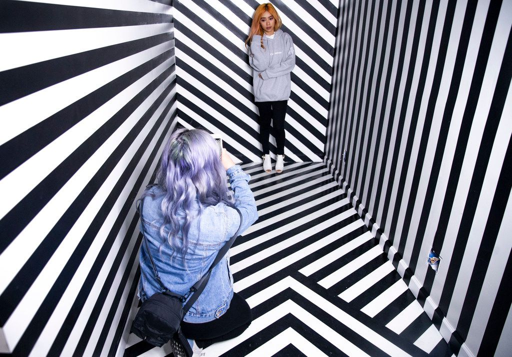 Linda Nguyen takes a picture of her sister, Jimmie Nguyen, both of Fort Worth, during a soft opening night at Rainbow Vomit on Thursday, Jan. 17, 2019. Rainbow Vomit is a new immersive art installation that will open on Saturday, January 19, 2019. (Shaban Athuman/The Dallas Morning News)