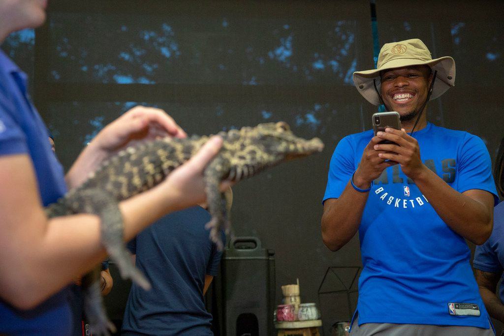 Dallas Mavericks players Dennis Smith Jr. takes a picture of Gimli, a 4 year-old African dwarf crocodile at the Dallas Zoo in August, 2018.