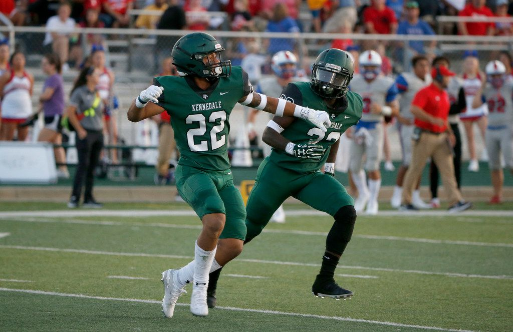 Kennedale's JD Coffey (22) celebrates his interception against Midlothian Heritage with teammate Frank Brooks (23) during the first half of their high school football game in Kennedale, Texas on September 6, 2019.