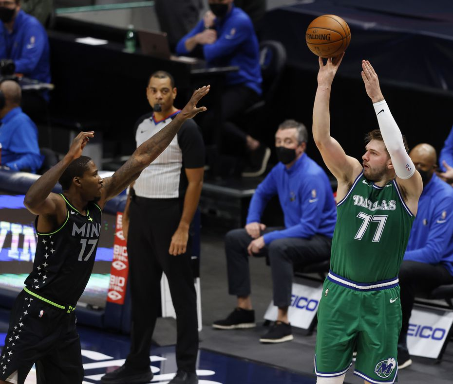 Mavericks guard Luka Doncic (77) attempts a shot over Timberwolves center Ed Davis (17) during the second quarter of play at American Airlines Center on Monday, Feb. 8, 2021, in Dallas.