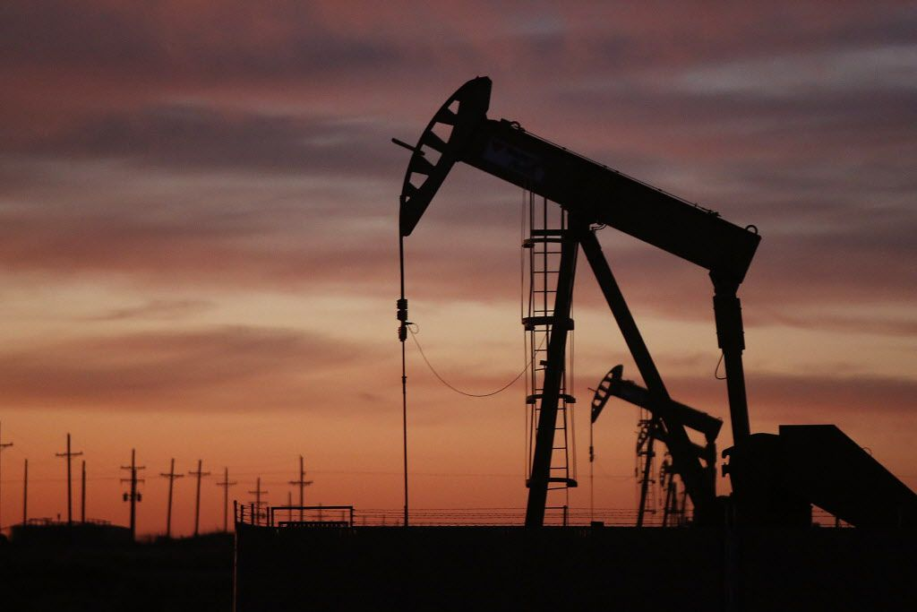 An oil pumpjack works at dawn in the Permian Basin oil field on Jan. 20, in the oil town of Andrews, Texas. The Lone Star State's economy has been hobbled by an ongoing price war between Saudi Arabia and Russia and a decrease in demand due to the coronavirus outbreak.