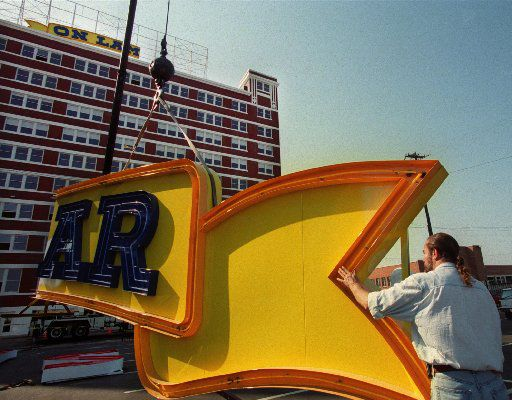 Designer Don Beck helped steady part of the neon sign that would read South Side on Lamar in 2000.