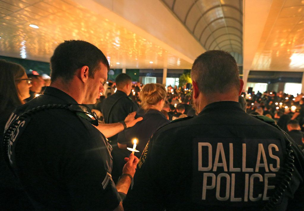 The roof of the Northeast Substation glows yellow from candlelight as the crowd joins in prayer at a candlelight vigil to support Dallas Police Officer Crystal Almeida, and to honor the memory of Officer Rogelio Santander, Jr., held at the Dallas Police Northeast Division substation on Thursday, April 26, 2018.