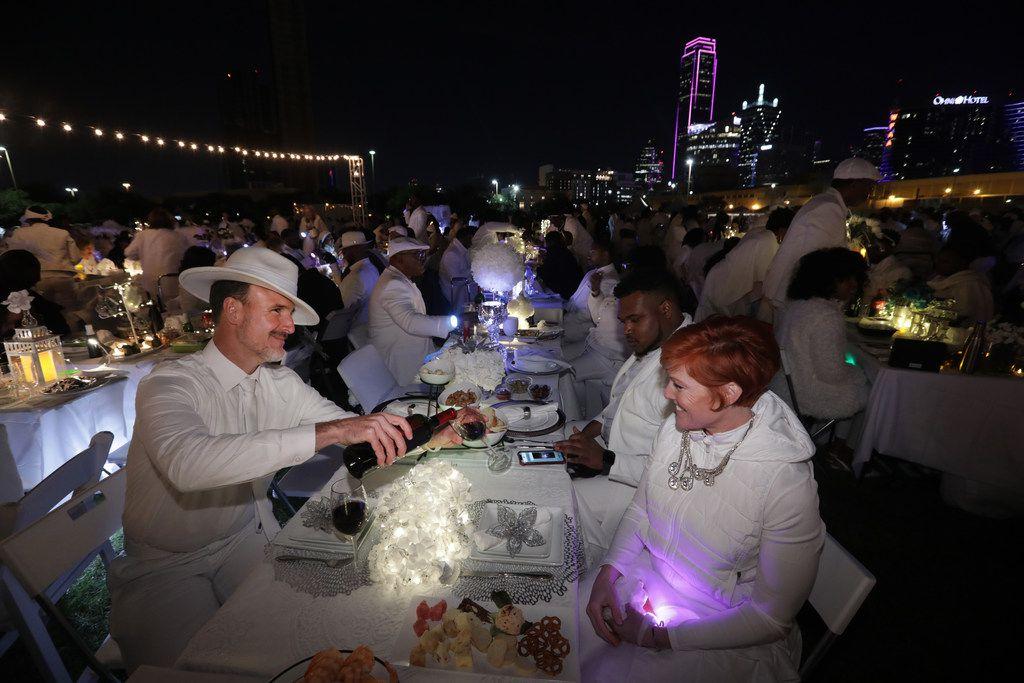Jon Reinke pours wine for Valery Reinke during a secret Diner en Blanc event at Reunion Park in Dallas on Nov. 9, 2018.