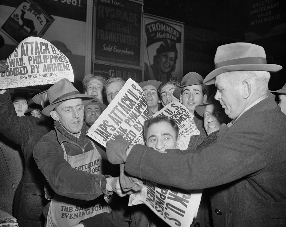 In this Dec. 7, 1941, file photo, people buy newspapers reporting the Japanese attack on U.S. bases in the Pacific Ocean, at Times Square in New York.