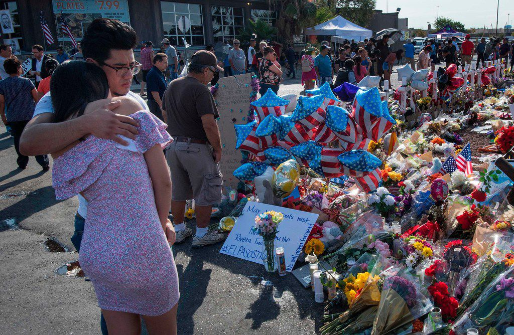 On Aug. 7, people hug at the makeshift memorial for victims of the Aug. 3 shooting at a Walmart in El Paso.