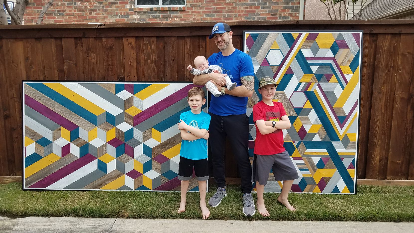Ryan Ekmark, 41, poses with his boys  — Caleb,10, Carter, 7, and Cayson 7 months — in front of his artwork.