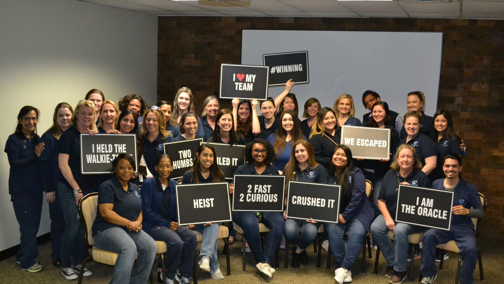 Cornea Associates of Texas workers celebrate after conquering an escape room challenge.