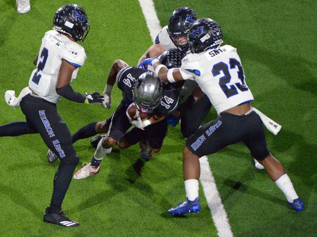 Guyer's Travis Romar (14) looks for running room between Hebron's William White (2) and Darius Snow (23) in the second half of a Class 6A Division II bi-district high school playoff football game between Hebron and Denton Guyer, Friday, Nov. 15, 2019, in Prosper, Texas. (Matt Strasen/Special Contributor)