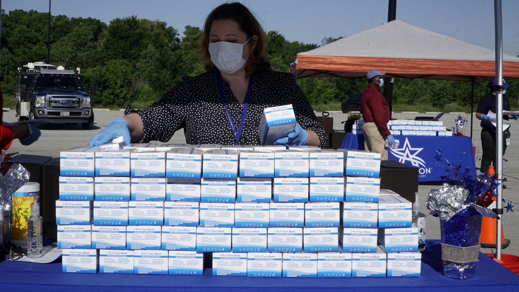 Susan Schrock keeps the supply flowing during a free mask giveaway in the parking lot at Globe Life Park in Arlington, Texas on Wednesday, May 6, 2020.  City of Arlington in partnership with Tarrant County, the Texas Rangers, Greater Arlington Chamber of Commerce, and Arlington Convention and Visitors Bureau provided protective masks for free to employees at Arlington businesses and restaurants.