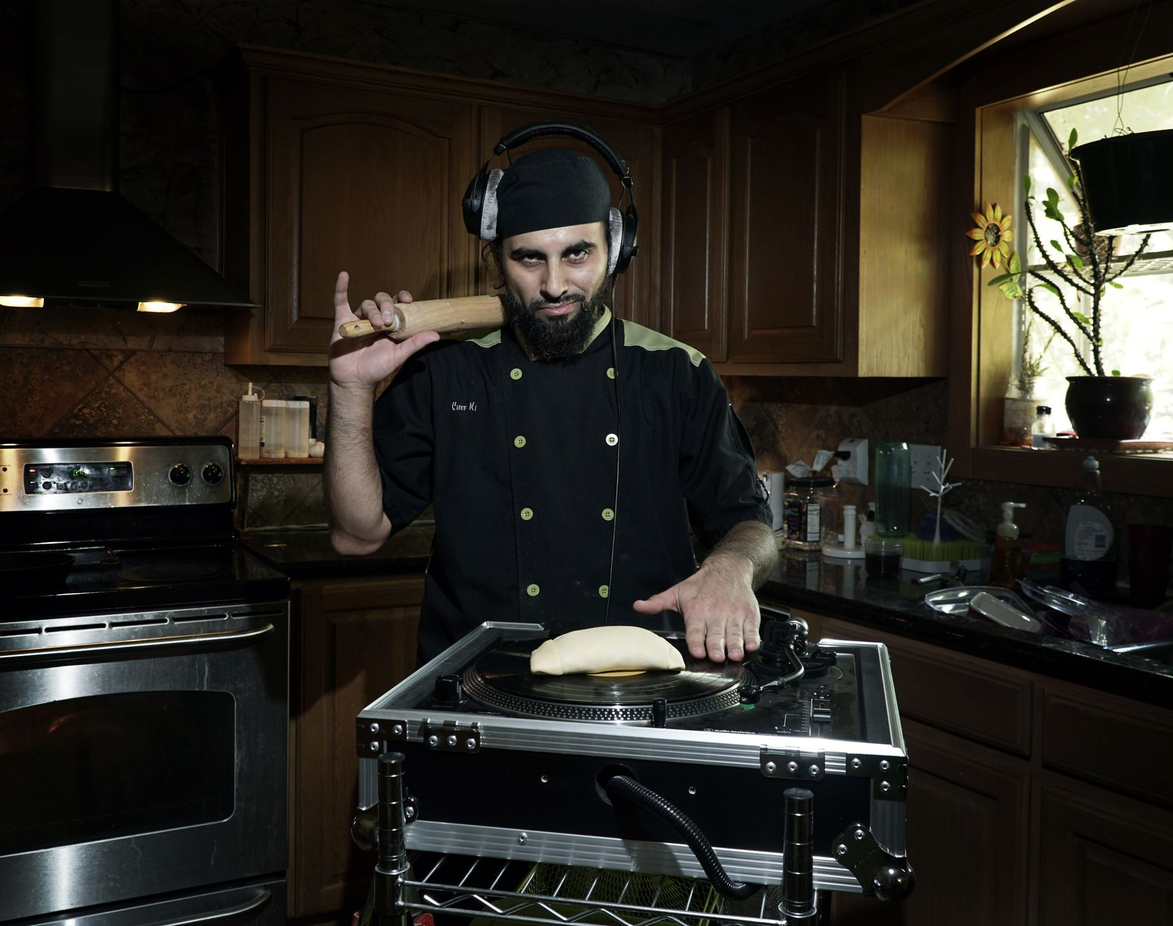 Local Chef and Hip Hop DJ Julio Cordonnier poses with his turn table and an empanada at his home in Euless.