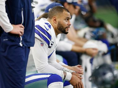 FILE - Cowboys quarterback Dak Prescott (4) sits on the bench during the second half of a game against the Buffalo Bills at AT&T Stadium in Arlington on Thursday, Nov. 28, 2019.
