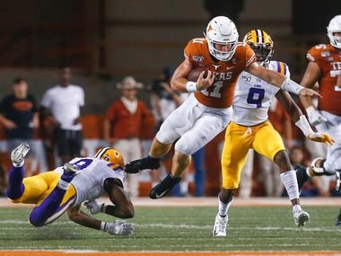 Texas Longhorns quarterback Sam Ehlinger (11) goes airborne in an attempt to evade LSU Tigers linebacker Patrick Queen (8) and safety Marcel Brooks (9) during the fourth quarter of a college football game between the University of Texas and Louisiana State University on Saturday, Sept. 7, 2019 at Darrell Royal Memorial Stadium in Austin, Texas.