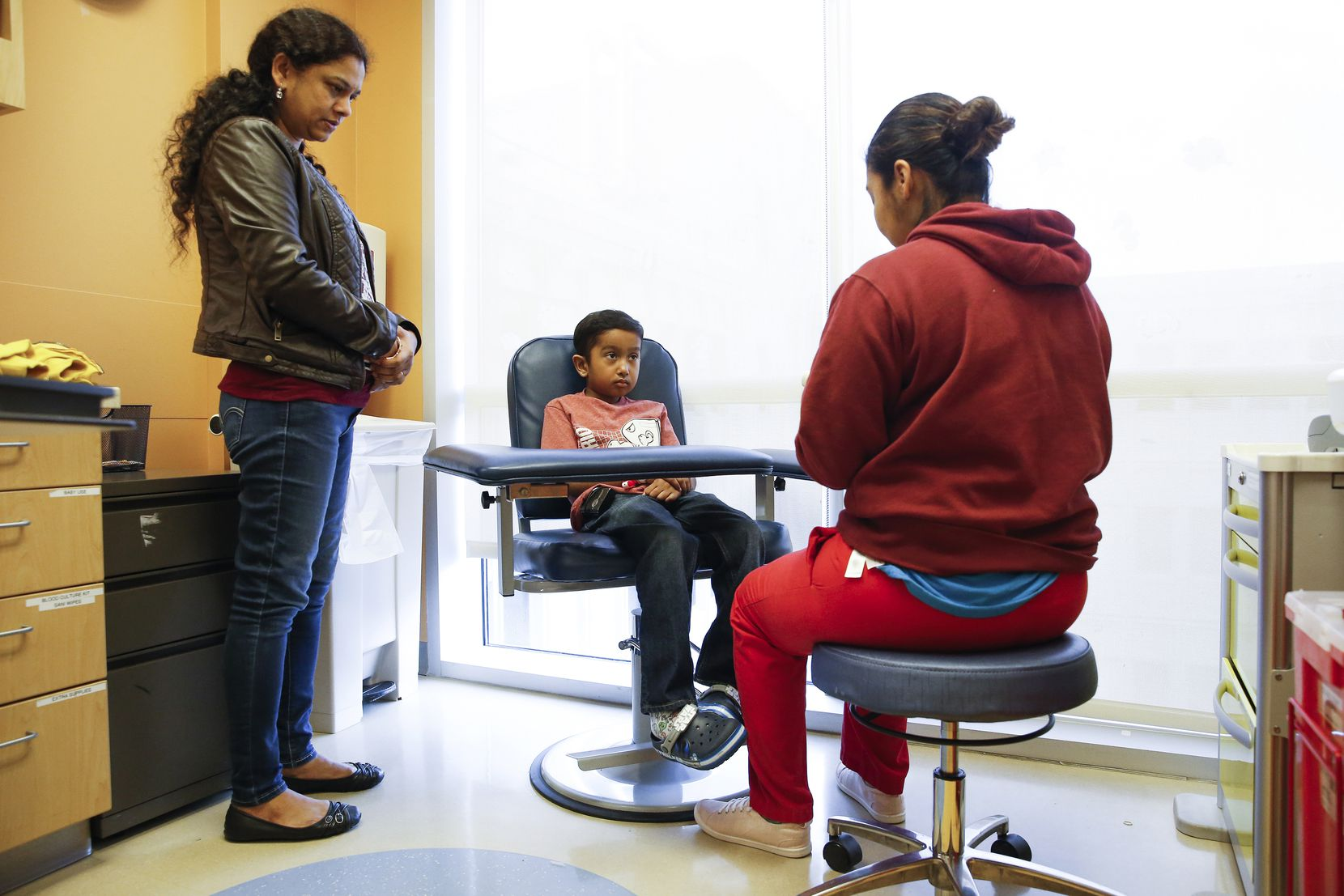 Akshaj Nagilla, 8, of Frisco, prepares to have his blood drawn during a checkup with his mother Anitha Nagilla, left, at Children's Medical Center Dallas on Friday, Feb. 7, 2020 in Dallas. In 2017, when Akshaj was six years old, he was diagnosed with leukemia and in desperate need of a bone marrow transplant. In August of 2017, he received his first transplant through the Be The Match donor program, which his family believes saved his life. After a relapse of the cancer in 2018 he needed a new transplant, which he received two days after Christmas in 2018. Today, Akshaj is now 8 years old and is still in remission, often visiting Children's Medical Center for checkups and blood work. (Ryan Michalesko/The Dallas Morning News)