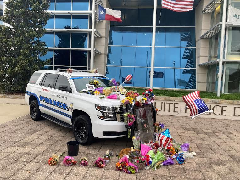 Toys, flowers and other offerings covered a Mesquite police car Tuesday in memory of Kozmo, a police K-9 killed in the line of duty.