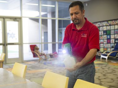 Raul Rodriguez mists the library at Daugherty Elementary School in Garland to disinfect it.
