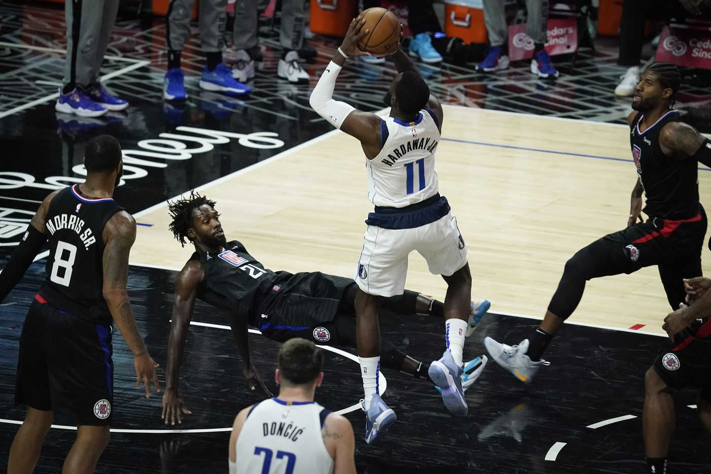 LA Clippers guard Patrick Beverley (21) falls to the ground as he picks up a foul on a drive by Dallas Mavericks forward Tim Hardaway Jr. (11) during the second half of an NBA playoff basketball game at Staples Center on Tuesday, May 25, 2021, in Los Angeles.